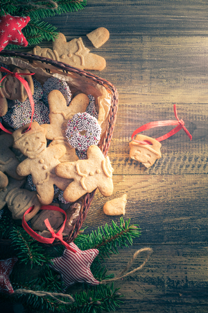 Christmas table: broken gingerbread in a basket full of sweets on a wooden table