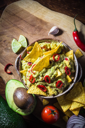 A bowl of guacamole with chips and ingredients: tomato, chilli pepper, lime, onion, garlic, dill