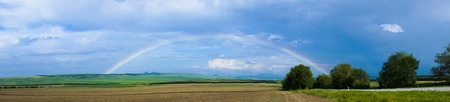 Panorama rainbow with clouds on a sunny day over the agricultural field photo