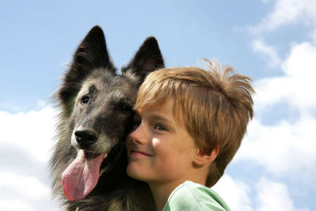 a cute 7-years old boy with his dog, a Belgian shepherd, photographed in the summer sun with blue sky and clouds in the background