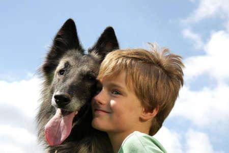 eine niedliche 7-Jahre alten junge mit seinen Hund, eine belgische Hirten, fotografiert in Sommer Sonne mit blauer Himmel und Wolken im Hintergrund