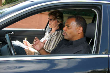 a mature African - American man having a driving test and being stressed out by the tester