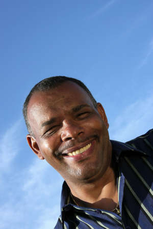 a smiling mature African - American man photographed in the summer sun with blue sky and clouds in the background