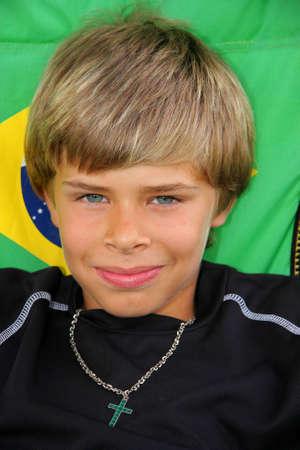 Retrato de un niño de América-alemán de edad de 10 años guapo sonriente sentado en una silla plegable de campamento con un banner de Brasilien