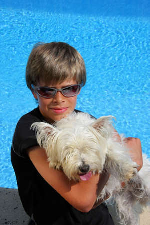a smiling handsome 10-years old boy with sunglasses holding his pet, a West Thailand terrier, in his arms while sitting at a swimming pool in the summer sun photo
