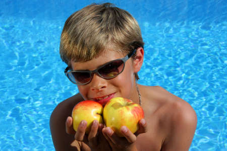 a 10-years old smiling American - German boy with sunglasses sitting at a swimming pool and presenting delicious apples in the summer sun photo