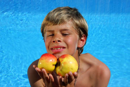 a 10-years old smiling American - German boy sitting at a swimming pool and presenting delicious apples in the summer sun photo