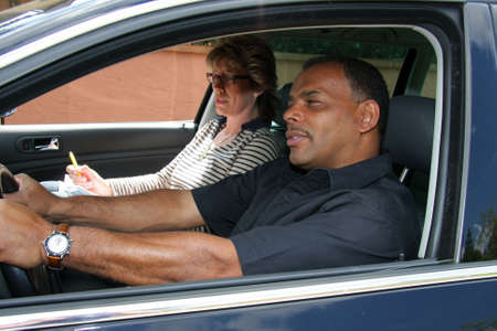 ein reifer African-American Mann, die mit einer Fahrprüfung und wird vom Tester gestresst