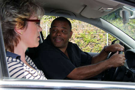 a mature African-American man having a driving lesson and trying to park into a parking lot