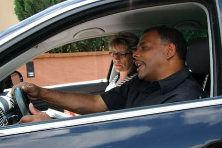 a mature African-American man having a driving test and being stressed out by the tester photo