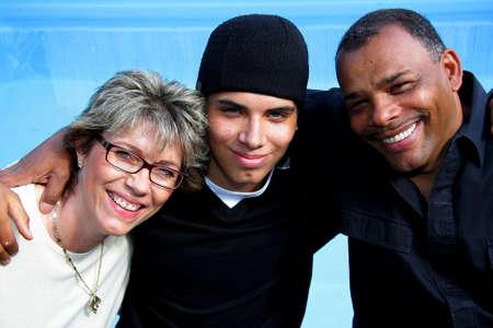 Eine glückliche amerikanisch-deutschen Familie mit Mutter, Vater und Sohn, die in der Sommersonne mit Swimmingpool im Hintergrund fotografiert  Standard-Bild - 5756190