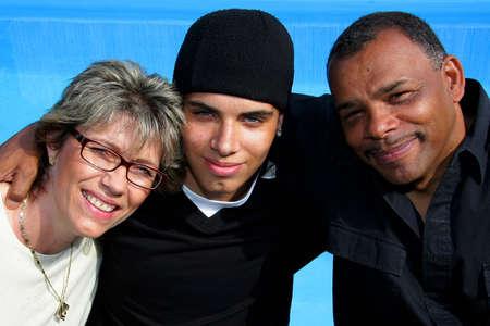 eine glückliche amerikanisch-deutschen Familie mit Mutter, Vater und ihren Teenager-Sohn, fotografiert in der Sommersonne an einen pool  Standard-Bild
