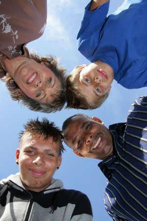 een Duits-Amerikaanse en gelukkige familie met moeder, vader en hun twee zonen, gefotografeerd vanaf omlaag naar de hemel met zak lamp met de blauwe lucht en de wolken in de achtergrond