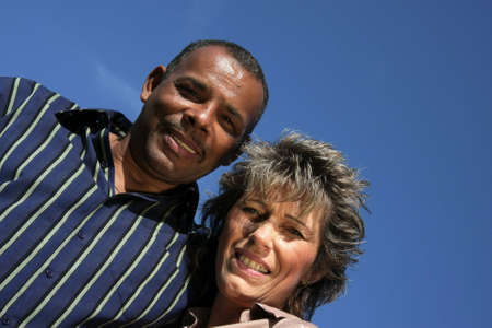 a happy and smiling American-German married couple photographed in the summer sun with blue sky and tiny clouds in the background photo