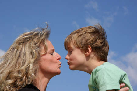 a beautiful mother giving a kiss to her cute 7-years old son photographed in the summer sun with blue sky and clouds in the background photo