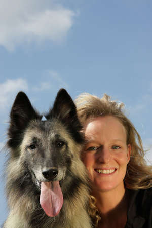 trusty: a beautiful smiling woman with her dog, a Belgian shepherd, photographed in the summer sun with blue sky and clouds in the background
