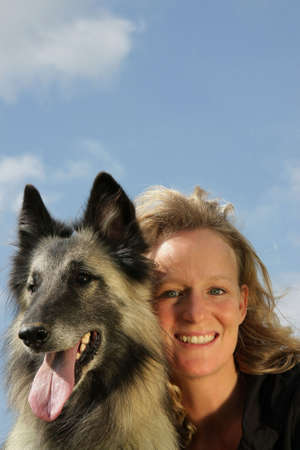 a beautiful smiling woman with her dog, a Belgian shepherd, photographed in the summer sun with blue sky and clouds in the background photo
