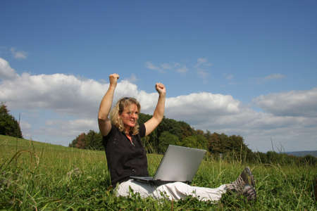 jubilating: an jubilating woman with a laptop sitting in the meadow and raising her arms towards sky, photographed in the summer sun with trees, blue sky and clouds in the background