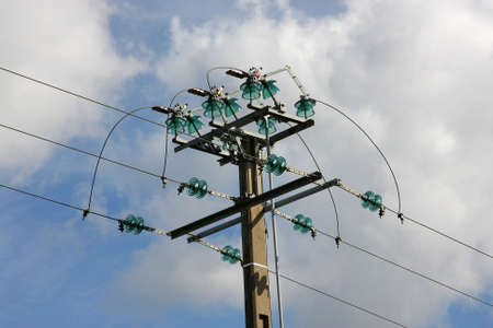 isolators: an electrical tower photographed in the summer sun with blue and cloudy sky in the background