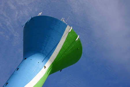 a colourful water tower, painted in blue, green and white, with cellular phone network antennas on top of it, photographed in the summer sun with blue and cloudy sky in the background Stock Photo - 5774516