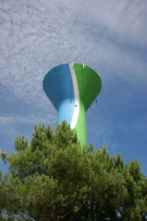 a colourful water tower, painted in blue, green and white, with cellular phone network antennas on top of it, photographed in the summer sun with blue and cloudy sky in the background photo