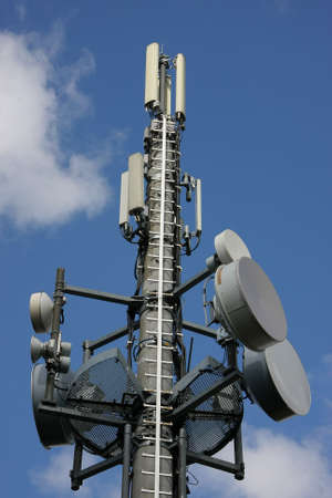a cellular phone network mast with different kind of antennas photographed in the summer sun with blue sky and clouds in the background