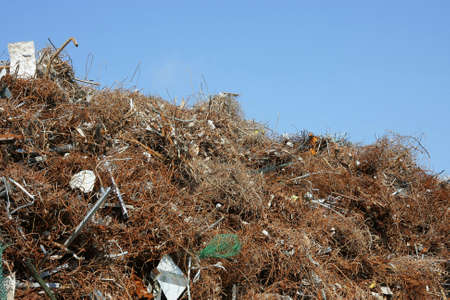 commercial recycling: a scrap heap with different kinds of metal photographed in the summer sun on a commercial recycling centre with blue sky in the background Stock Photo