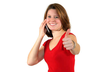a smiling beautiful young business woman with a cell phone posing with the thumbs up sign, isolated on white background photo