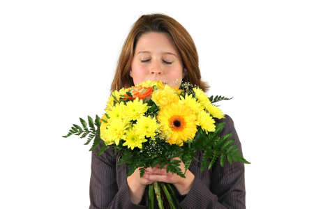 a beautiful young business woman smelling at a bunch of flowers with closed eyes, isolated on white background photo