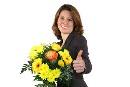 a smiling beautiful young business woman with a bunch of flowers posing with the thumbs up sign, isolated on white background photo