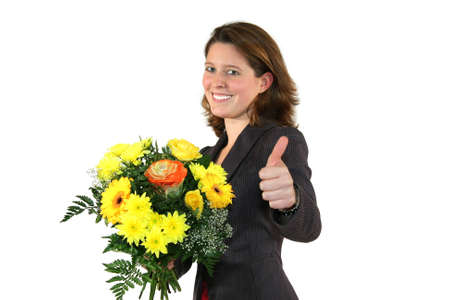 awarded: a smiling beautiful young business woman with a bunch of flowers posing with the thumbs up sign, isolated on white background Stock Photo