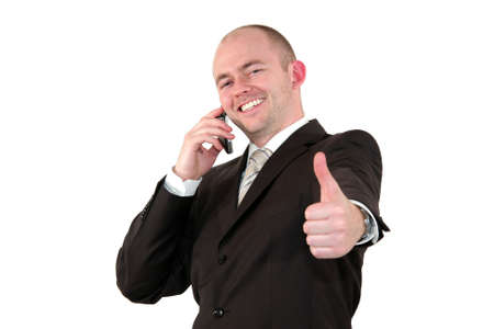 a smiling young business man with a cell phone posing with the thumbs up sign, isolated on white background
