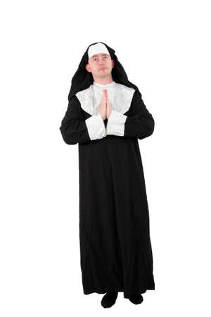 a male actor in a nun´s costume with praying hands and a view to the sky, isolated on white background photo