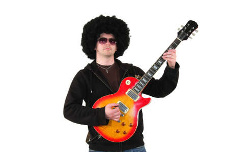 a young guitarist with a wig and sunglasses playing a colourful electrical guitar, isolated on white background photo