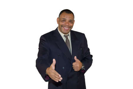 A smiling senior African-American businessman reaching out his hand for a welcoming handshake and posing with thumbs up, isolated on white background