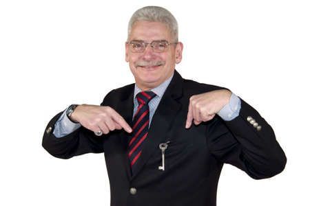 A smiling senior caucasian manager pointing at a key, isolated on white background photo