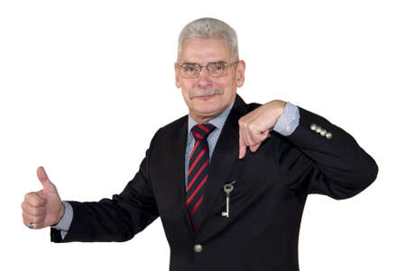 A smiling senior caucasian manager pointing at a key and posing with the thumbs up sign, isolated on white background photo