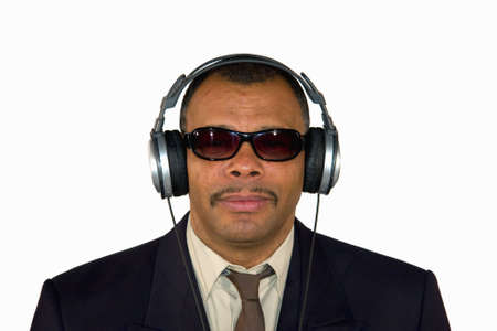 a serious looking mature Arfrican-American man with headphones and sunglasses, isolated on white background Stock Photo - 6473493