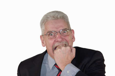 freaking: a caucasian senior manager freaking out and biting into his fist, isolated on white background Stock Photo