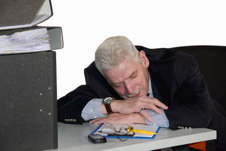 a caucasian senior manager having a power nap in his office, isolated on white background photo