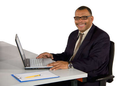 a smiling mature African-American businessman in his office with a laptop, isolated on white background Stock Photo