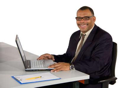 Lächelnd mündig US-amerikanischer Geschäftsmann in seinem Büro mit einem Laptop, isoliert auf weißem Hintergrund  Standard-Bild - 6473444