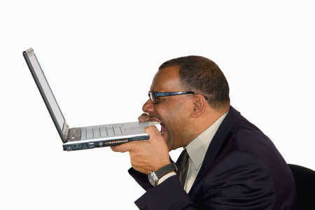 freaking: a frustrated mature African-American businessman biting into his laptop, isolated on white background