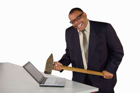 a laughing mature African-American businessman hitting his laptop with a sledgehammer, isolated on white background
