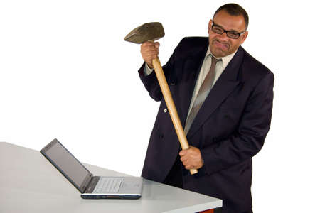 freaking: a fierce looking frustrated mature African-American businessman aiming with sledgehammer at his laptop, isolated on white background Stock Photo