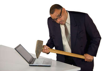 wrath: a fierce looking frustrated mature African-American businessman aiming with sledgehammer at his laptop, isolated on white background Stock Photo
