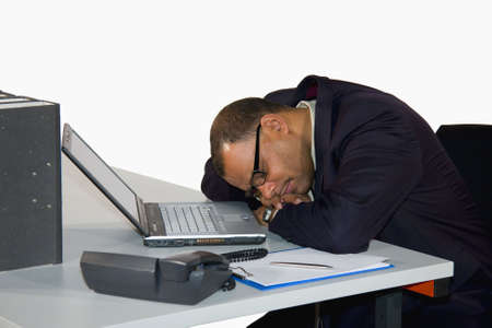 a mature African-American businessman having a power nap in his office, isolated on white background photo
