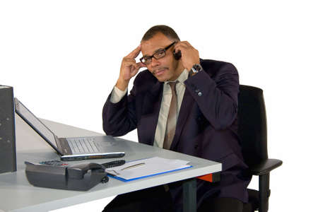 a concentrated mature African-American businessman being busy phoning, isolated on white background Standard-Bild