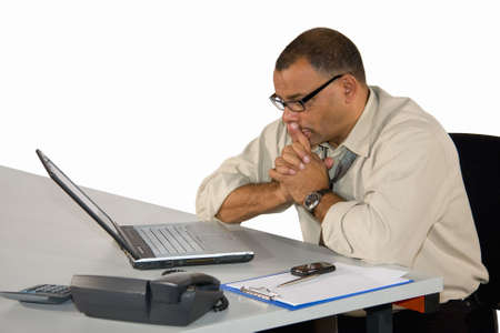 a concentrated mature African-American businessman working at his laptop, isolated on white background