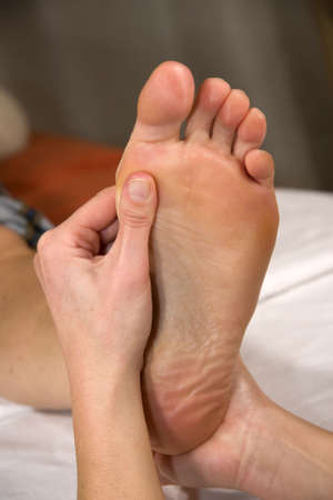 a closeup of a foot of a natural mature woman having a foot reflex zone massage at the ball of her foot photo